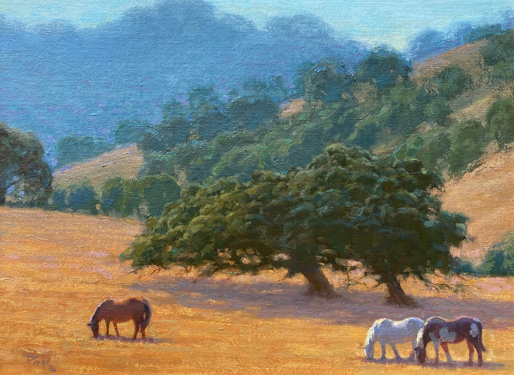 3 horses, two almost becoming one figure, graze peacefully in the midday sun in a golden field with two majestic oak trees.  Rolling oak-covered hills rise in the distance.