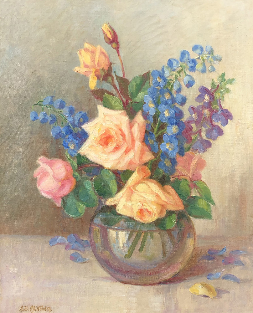 A still life of colorful multi-colored roses and other flowers in a clear vase on a table.