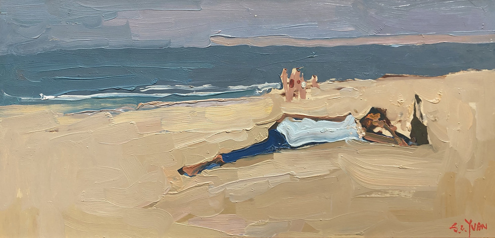 A woman lying on the sand at a beach near Monterey, California.
