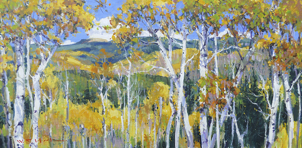A mountainous New Mexico landscape seen through colorful aspen trees.