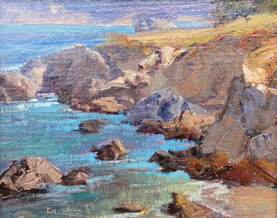 Calm waters and shadowed rocks on a coastal cliff in Pacific Grove, CA.