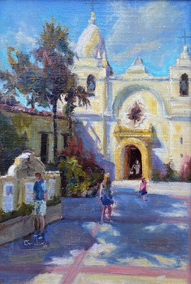 Visitors stroll along the walkway to the front entrance to the historic Carmel Mission in Carmel, California.