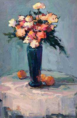 A colorful still life of multi-colored flowers in a blue vase on a table with a white tablecloth and three persimmons.