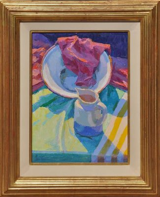 A colorful still life of a tabletop with a white bowl, red napkin and white and blue creamer on a multi-colored tablecloth, all in sunlight and shadow.