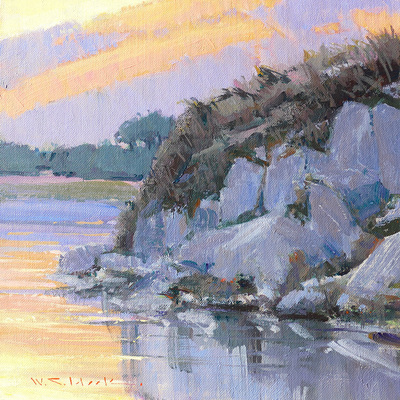 Dusk falls on rocks at the mouth of the Carmel River. Evening light casts colorful shadows on the sky and water.